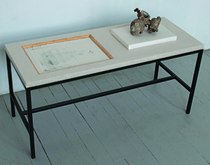 M. Benjamin Herndon Scholar's Rock, No. 1, 2014 Found carburetor; paper and wood tabletop, metal base; six photolithographs on Japanese paper inset in table. Table: 40 X 16 X 19 inches; carburetor: 6 X 8 X 6 inches